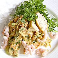 Krydret kyllingsalat med reker og grønnsaker servert i naanbrød -