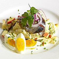 Kryddersild med potet, eple og rødbetsalat, smilende egg servert på grovbrød -