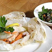 Ovnsbakt laks og steinbit servert med grønne linser -