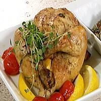 Helstekt fylt kylling med urter og sitron, servert på en seng av linser og grønnsaker -