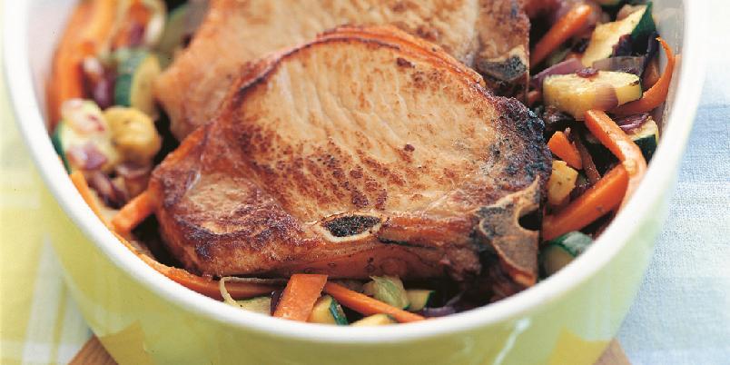 Koteletter og grønnsaker i ovn - Kotelettene forhåndsstekes i panne, før de legges på en grønnsakssseng i ovnen.
