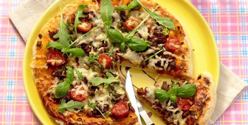 """Pizza med kjøttdeig og rucola - Pizzaen kan dateres så langt tilbake som til romernes tid. Selve navnet stammer fra det latinske ordet """"picea"""", som beskriver sotingen av skorpen når pizzaen stekes over åpen varme – for det gjorde man i begynnelsen. Lag porsjonspizzaer. Slik at alle kan bestemme hva de vil ha som fyll."""