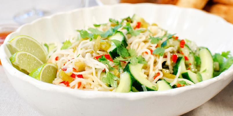 Nudelsalat med agurk og koriander - Det er helt opp til deg om du vil servere denne nudelsalaten varm eller kald. Den smaker veldig godt samme hva. Før jeg blander selve salaten, lager jeg dressingen. Syren i den gjør at vårløken får nærmest en syltet smak.