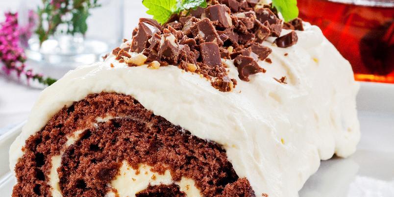 Rullekake med vaniljekrem og firkløver - Rull en sjokoladekake! Denne rullekaken smaker himmelsk godt av sjokolade, vaniljekrem og hasselnøtter.