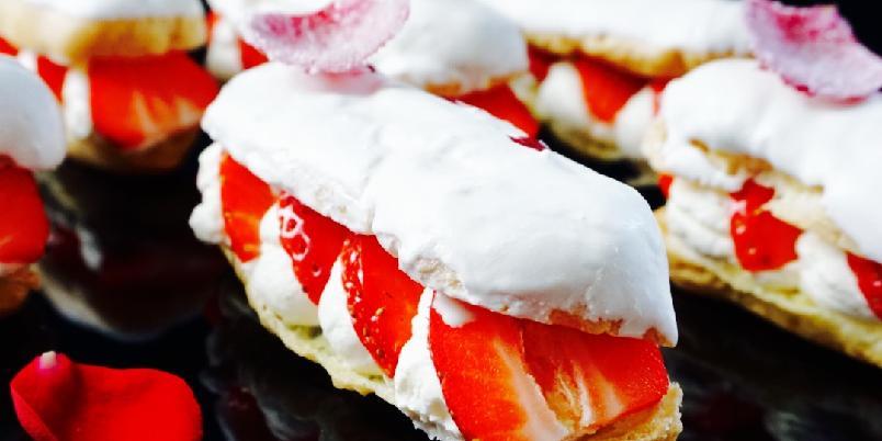 Eclairs - Her har du oppskriften på luftige vannbakkels fylt med krem og jordbær. Lokket er dyppet i hvit sjokolade og pyntet med et roseblad.