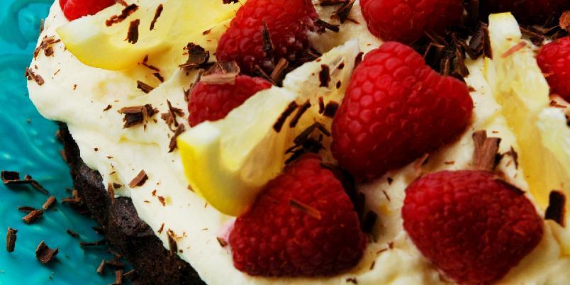 Chocolate chunk brownies med kremostglasur - Rask å lage, og utrolig kjekk å slenge sammen når du får uventet besøk, eller når du plutselig får lyst på noe godt! Denne brownien er proppfull av sjokolade og toppet med nydelig kremostglasur av hvit sjokolade og sitron, og ferske bringebær. Oppskriften er nok til en springform á 20 cm.