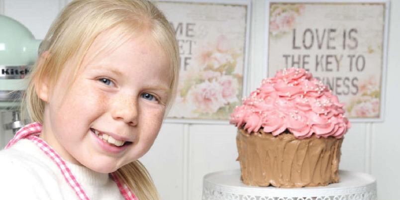 Kjempecupcake - En sjokoladekake formet som en cupcake i samspill med rosa topping utgjør en kjempecupcake, til barnas store fornøyelse.