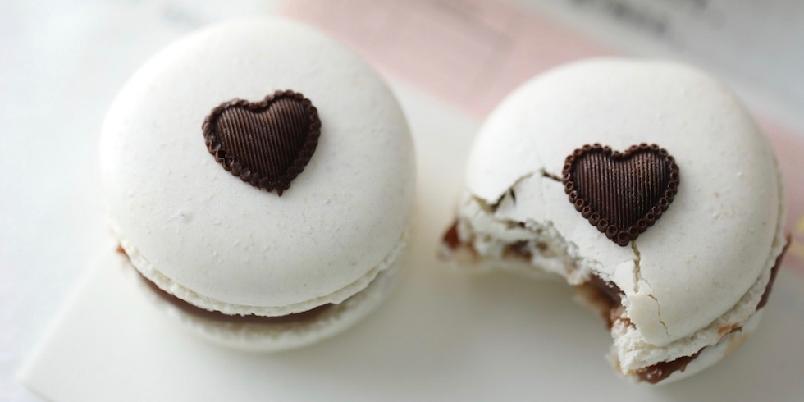 Hvite makroner med lys sjokoladefudge - Dette er vaniljemakroner uten fargetilsettinger, og toppet med et brunt sjokoladehjerte. Fyllet er en lys sjokoladefudge, og den smaker nesten som smørbukk.